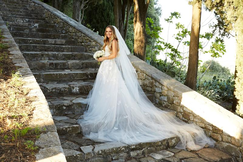 Caroline on the steps leading up to the castle ruins in her custom ordered Oscar de la Renta fern and floral lace embroidered gown.