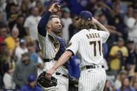 Milwaukee Brewers' Josh Hader and Manny Pina celebrate after a baseball game against the Chicago Cubs Saturday, Sept. 18, 2021, in Milwaukee. The Brewers won 6-4 and clinched a spot in the 2021 Postseason. (AP Photo/Morry Gash)