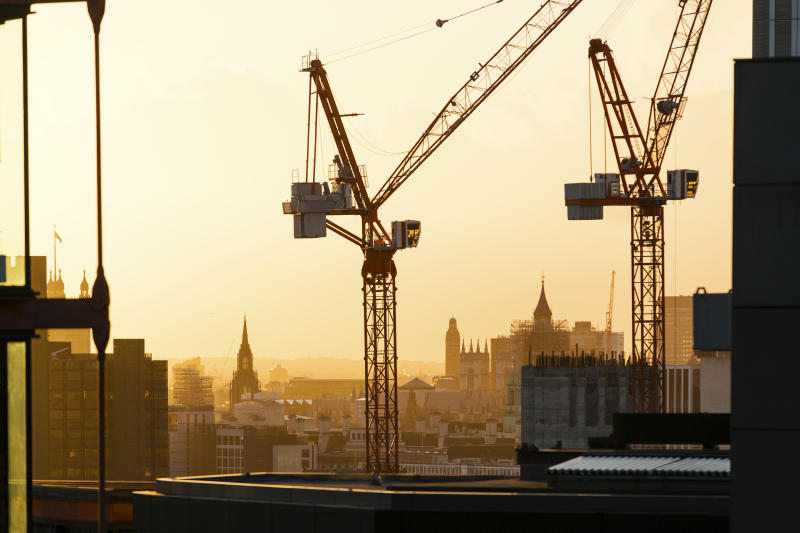 London skyline at sunset and silhouettes of construction cranes
