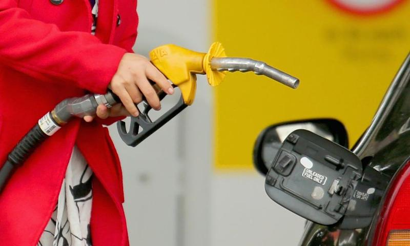A woman uses a fuel dispenser to fill her car up with petrol at a petrol station