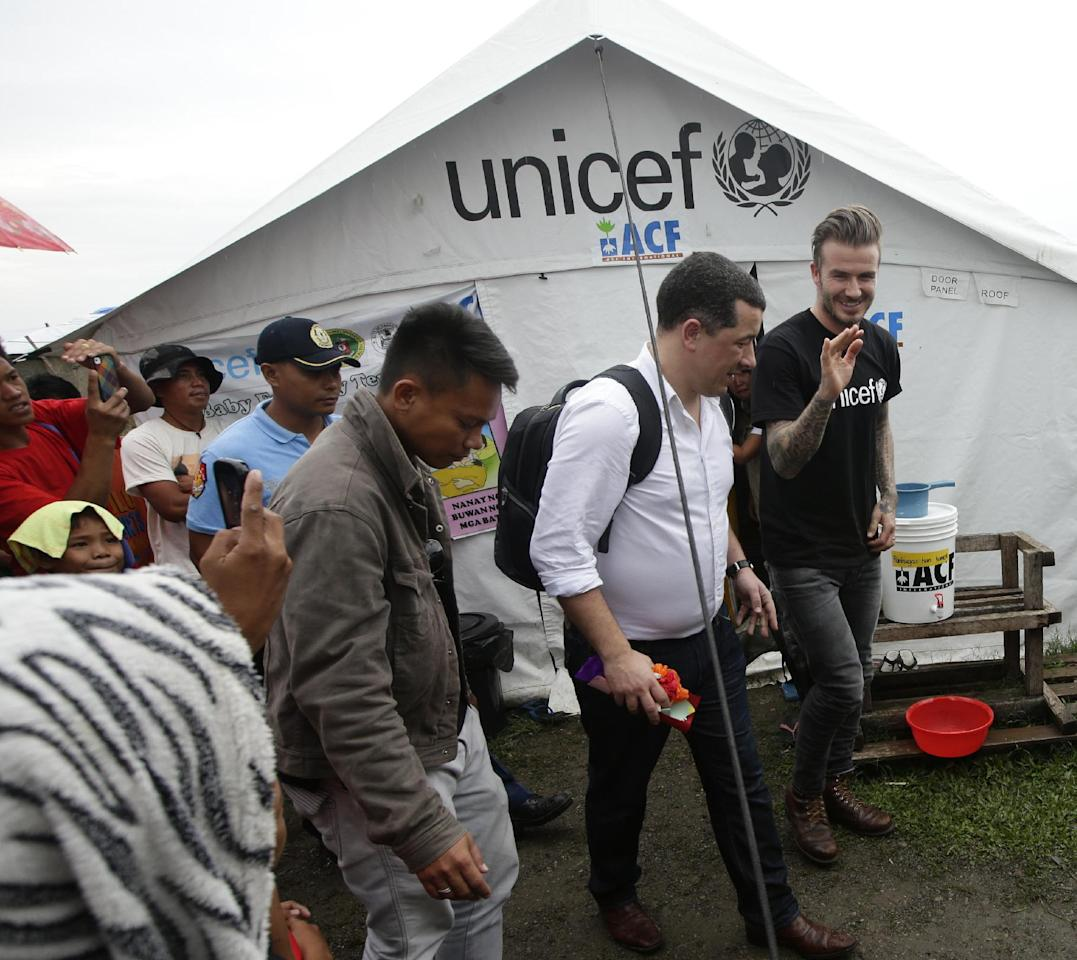 Former England soccer team captain David Beckham emerges from a tent after interacting with typhoon survivors during his visit nearly a hundred days after typhoon Haiyan (local name Yolanda) devastated Tacloban city and other provinces in central Philippines Thursday, Feb. 13, 2014. Beckham and his wife were one of several international celebrities to raise funds for typhoon victims. (AP Photo/Bullit Marquez)