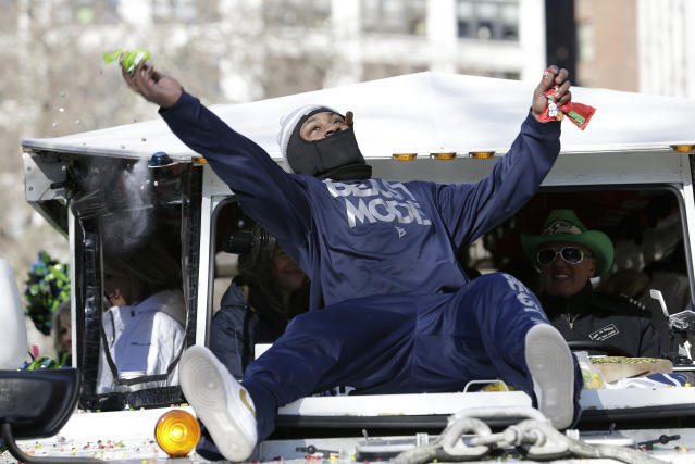 Seattle Seahawks' running back Marshawn Lynch throws pieces of Skittles candy while riding on the hood of a vehicle during the Super Bowl champions parade on Wednesday, Feb. 5, 2014, in Seattle. The Seahawks beat the Denver Broncos 43-8 in NFL football's Super Bowl XLVIII on Sunday. (AP Photo/Elaine Thompson)