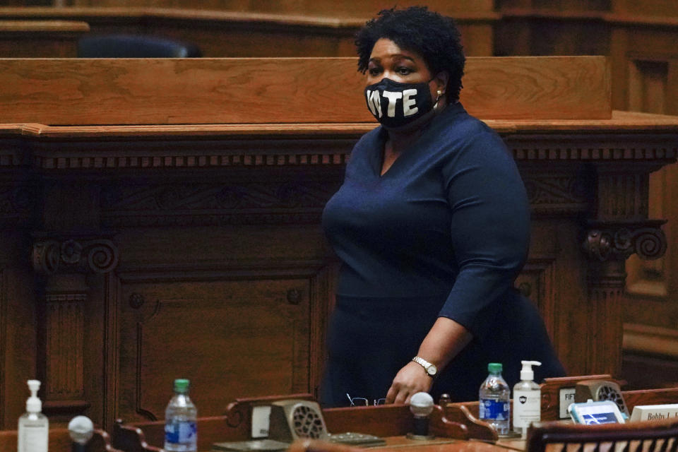 Democrat Stacey Abrams, walks on Senate floor before of members of Georgia's Electoral College cast their votes at the state Capitol, Monday, Dec. 14, 2020, in Atlanta. (AP Photo/John Bazemore, Pool)