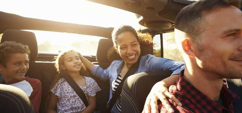Happy family in a car with sunroof open