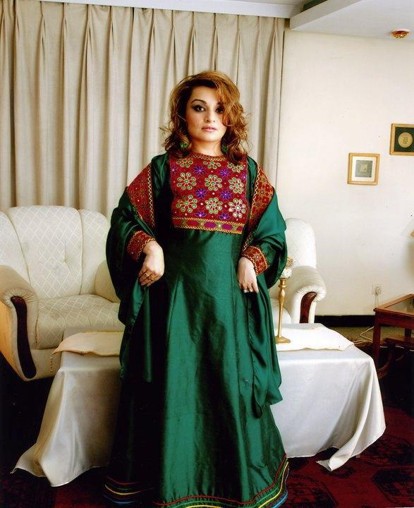 A woman poses in traditional Afghan attire, in Kabul