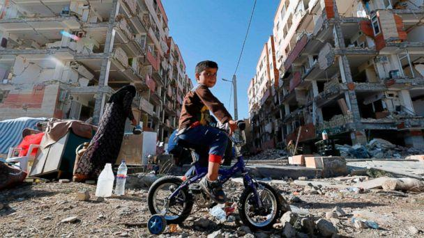 PHOTO: A boy rides a bicycle past earthquake damaged buildings in the town of Sarpol-e Zahab in Iran's western Kermanshah province near the border with Iraq, Nov. 14, 2017. A powerful earthquake struck the region on Nov. 12. (Atta Kenareatta/AFP/Getty Images)