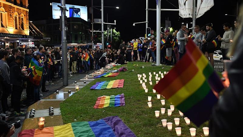 People gather at a vigil in solidarity for the victims of the Orlando nightclub mass shooting at Taylor Square. Photo: AAP