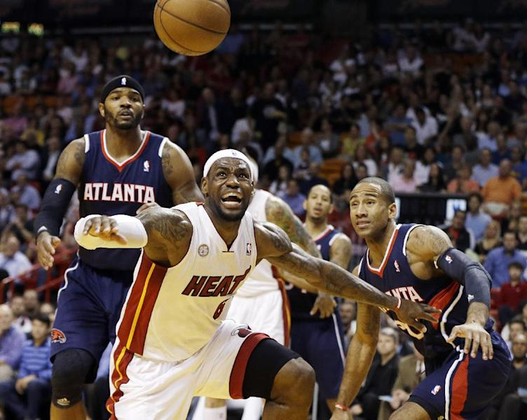 Miami Heat's LeBron James (6) forces Atlanta Hawks' Dahntay Jones (30) away from the ball during the first half of an NBA basketball game in Miami, Tuesday, March 12, 2013. (AP Photo/J Pat Carter)