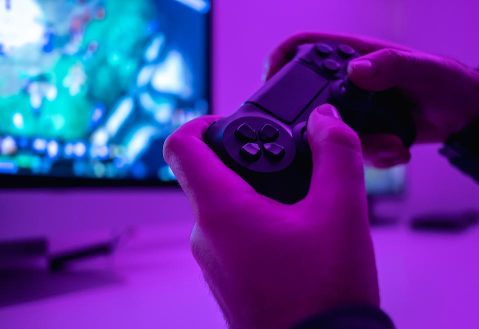 Closeup hands of anonymous male holding modern controller while playing video game in dark room