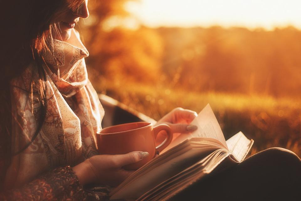 woman reading a book outside at sunset holding a cup, reducing alzheimer's risk