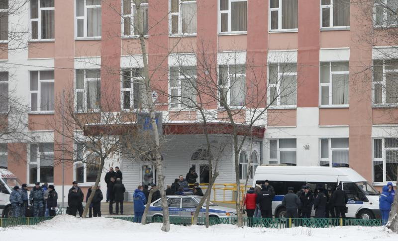 Interior Ministry members in uniform and other authorities gather outside a high school, where a student shot a teacher and a police officer dead and held more than 20 other students hostage, on the outskirts of Moscow