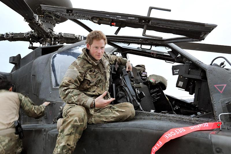In this photo taken Dec. 12, 2012, made available Monday Jan. 21, 2013 of Britain's Prince Harry or just plain Captain Wales as he is known in the British Army, talks to a TV crew after making his early morning pre-flight checks on the flight-line, from Camp Bastion southern Afghanistan. The Ministry of Defense announced Monday that the 28-year-old prince is returning from a 20-week deployment in Afghanistan, where he served as an Apache helicopter pilot with the Army Air Corps. (AP Photo/ John Stillwell, Pool)