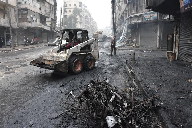 A tractor removes rubble as the Syrian government starts to clean up areas formerly held by opposition forces in the northern city of Aleppo on December 27, 2016, in the Shaar district (AFP Photo/George OURFALIAN)