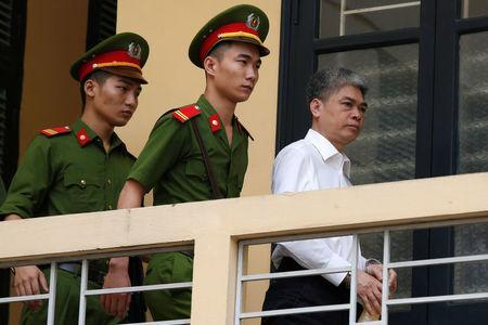 Former Petro Vietnam (PVN) chairman Nguyen Xuan Son (R) is escorted by police as he leaves the court after the verdict session in Hanoi, Vietnam September 29, 2017. REUTERS/Kham