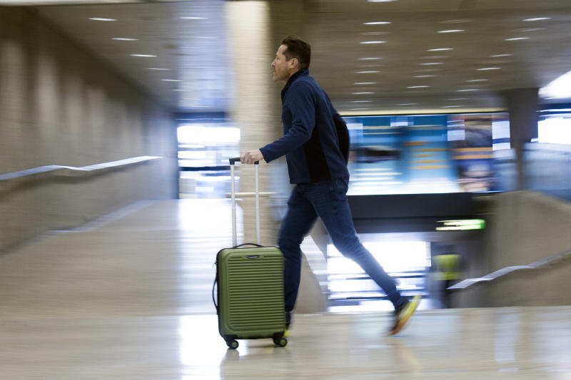 An airline passenger runs through the terminal at Dulles International Airport in Dulles, Va., Tuesday, March 26, 2019. (AP Photo/Cliff Owen)