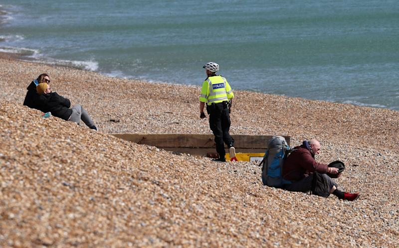A police officer asks people to leave the beach in Brighton, south England, as the UK continues to implement a social lockdown. (Photo: ASSOCIATED PRESS)