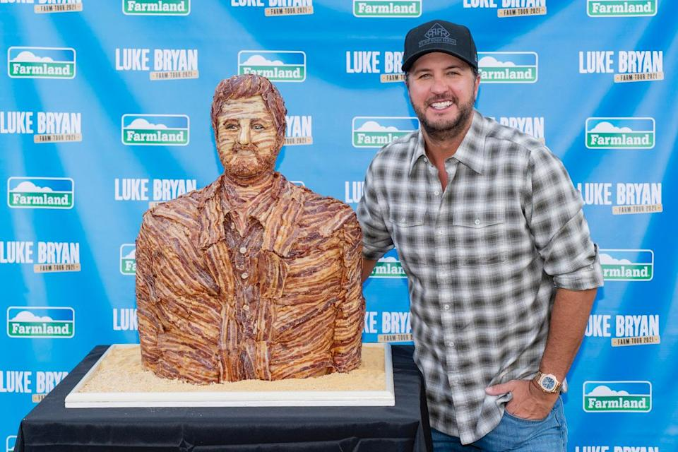 <p>Luke Bryan poses with a statue of himself made entirely of Farmland bacon at his Farm Tour 2021 stop in Marshall, Wisconsin, on Sept. 6.</p>