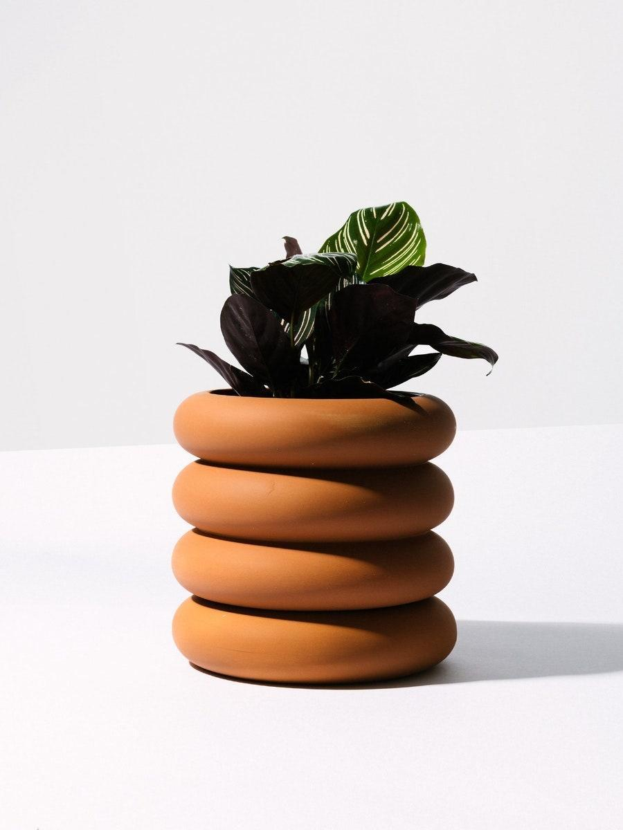 """Plant parents will appreciate this thoughtfully-designed stacking planter from Chen Chen & Kai Williams. It features a discreet saucer affixed to the bottom (meaning no water rings on their new sill!). $90, Homecoming. <a href=""""https://home-coming.com/products/areaware-terra-cotta-stacked-planter-tall"""" rel=""""nofollow noopener"""" target=""""_blank"""" data-ylk=""""slk:Get it now!"""" class=""""link rapid-noclick-resp"""">Get it now!</a>"""