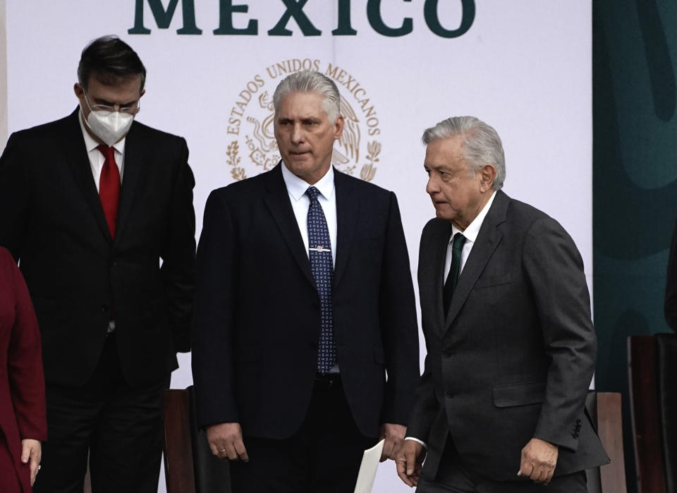 Cuba's Miguel Diaz-Canel, center, accompanies Mexico President Andres Manuel Lopez Obrador, during Independence Day celebrations in the Zocalo in Mexico City, Thursday, Sept. 16, 2021. (AP Photo/Marco Ugarte)