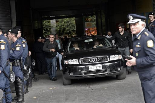 <p>EU and IMF officials are escorted out from the emergency exit of the Greek Finance Ministry after their meeting with the Greek Finance Minister while protesters gathered outside the ministry in Athens on November 5, 2013</p>