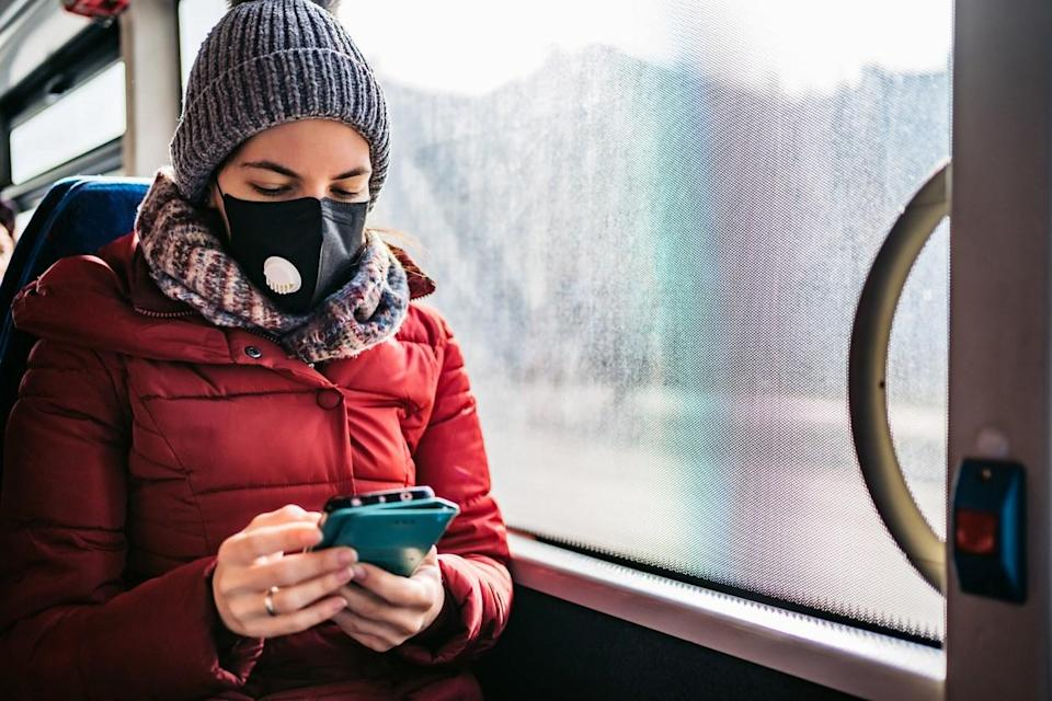 A young woman wearing a winter hat, scarf, and coat checks her smartphone while riding a bus