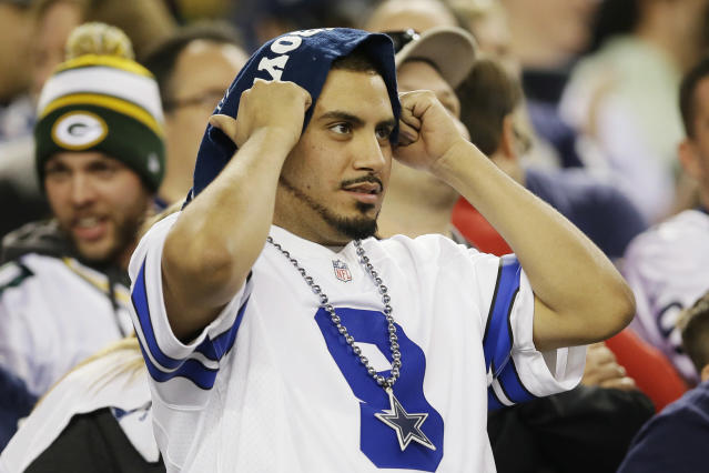 A Dallas Cowboys fan watches action against the Green Bay Packers during the second half of an NFL football game, Sunday, Dec. 15, 2013, in Arlington, Texas. (AP Photo/Tony Gutierrez)