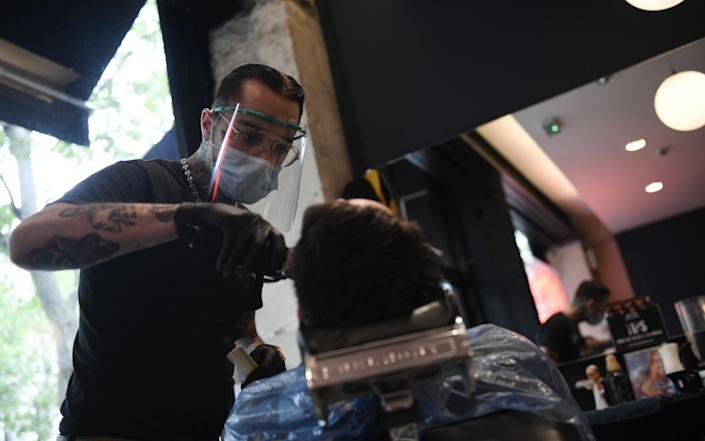 Hairdresser wearing a protective face mask gives a haircut to a customer at a barber shop in Paris, France, 11 May 2020. - Julien de Rosa/EPA-EFE/Shutterstock/ Shutterstock