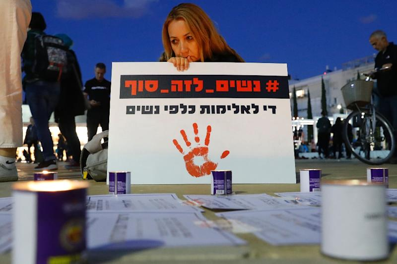 "An Israeli woman holds a placard which reads in Hebrew ""Stop the violence against women"" during a rally in Tel Aviv on December 4, 2018"