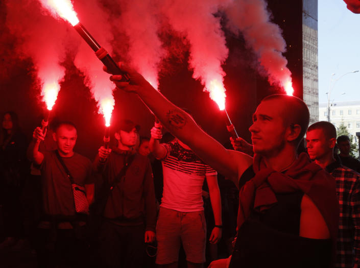 FILE - In this Sept. 5, 2019, file photo, volunteers with the right-wing paramilitary Azov National Corps light flares during a rally at the appeals court, as they protest against release Volodymyr Tsemakh, former commander of Russian-backed separatist forces in eastern Ukraine, in Kiev, Ukraine. Tensions are rising over the conflict in eastern Ukraine, with growing violations of a cease-fire and a massive Russian military buildup near its border with the region. (AP Photo/Efrem Lukatsky, File)