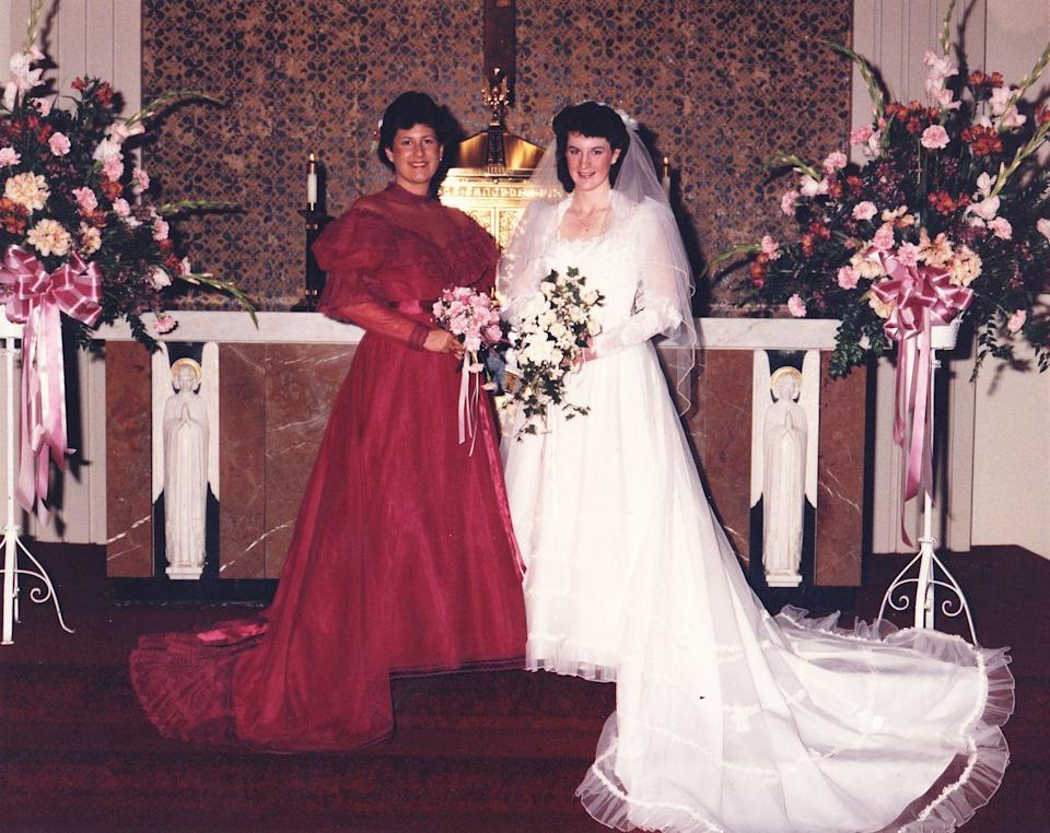 <p>Lace ruled formal gowns of the '80s, as seen in this 1985 wedding. The deep red bridesmaid dress picks up the darker hues within the bride's bouquet.</p>
