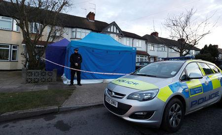 A police officer stands guard outside the home of Nikolai Glushkov in New Malden