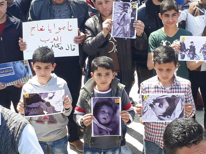 Children in Khan Sheikhoun hold pictures of children killed in a chemical weapons attack earlier this week in a demonstration in support of US intervention in the Syrian conflict on Friday April 7, 2017: Idlib Media Centre