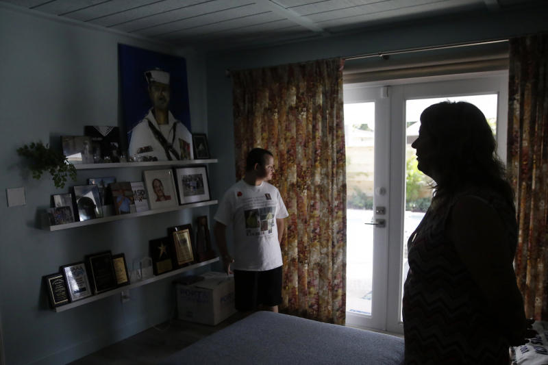 """Corey Hixon, 24, left, and Debbi Hixon, right, stand in a renovated room with memorabilia of Chris Hixon, a victim of the Parkland school shooting on the second anniversary of his death Friday, Feb. 14, 2020, in Hollywood, Fla. """"He's still part of our family and I didn't want it to feel like he's not here anymore,"""" she said of the home renovation completed during a whirlwind 10-days for the show """"Military Makeovers."""" (AP Photo/Brynn Anderson)"""