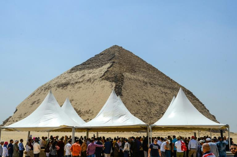 People gather for a ceremony in front of the Bent Pyramid of King Sneferu in the ancient royal necropolis of Dahshur south of Cairo on July 13, 2019