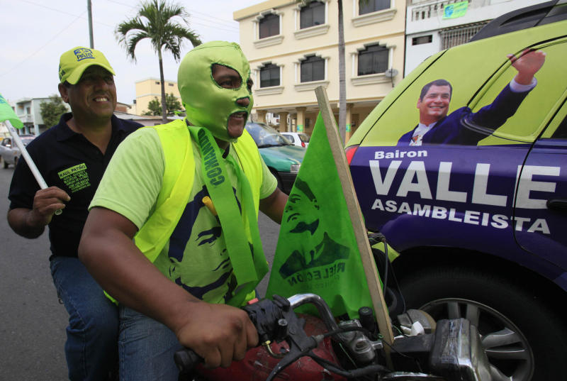 People attend a rally of Ecuador's President and candidate for re-election Rafael Correa, next to an image of him, right, in Guayaquil, Ecuador, Wednesday, Feb. 13, 2013. Presidential elections in Ecuador are scheduled for Feb. 17. (AP Photo/Dolores Ochoa)