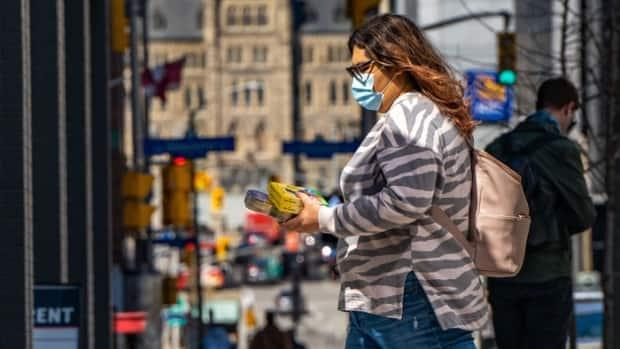 A woman wearing a mask walks near Parliament Hill in Ottawa on April 3, 2021. (Mathieu Theriault/Radio-Canada - image credit)