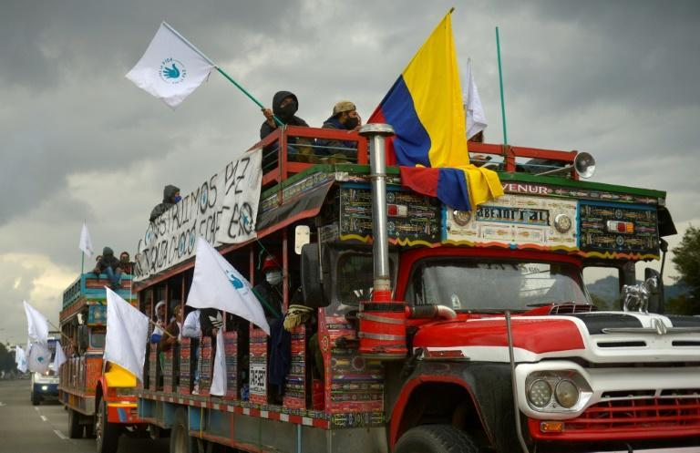 """Former FARC guerrilla members riding in """"chivas"""" (local transport vehicles) arrive in Bogota, Colombia to protest the murder of hundreds of ex-combatants"""