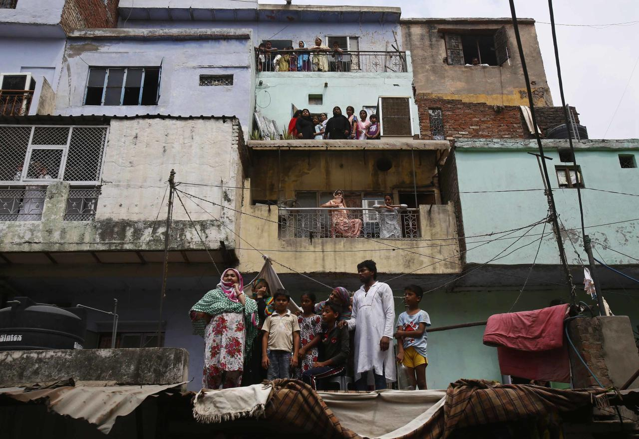Local residents watch the site of a collapsed building in New Delhi June 28, 2014. A decades-old building collapsed in New Delhi on Saturday killing at least 10, local media has reported, highlighting the need to monitor construction across India where such incidents are commonplace. REUTERS/Anindito Mukherjee (INDIA - Tags: DISASTER)