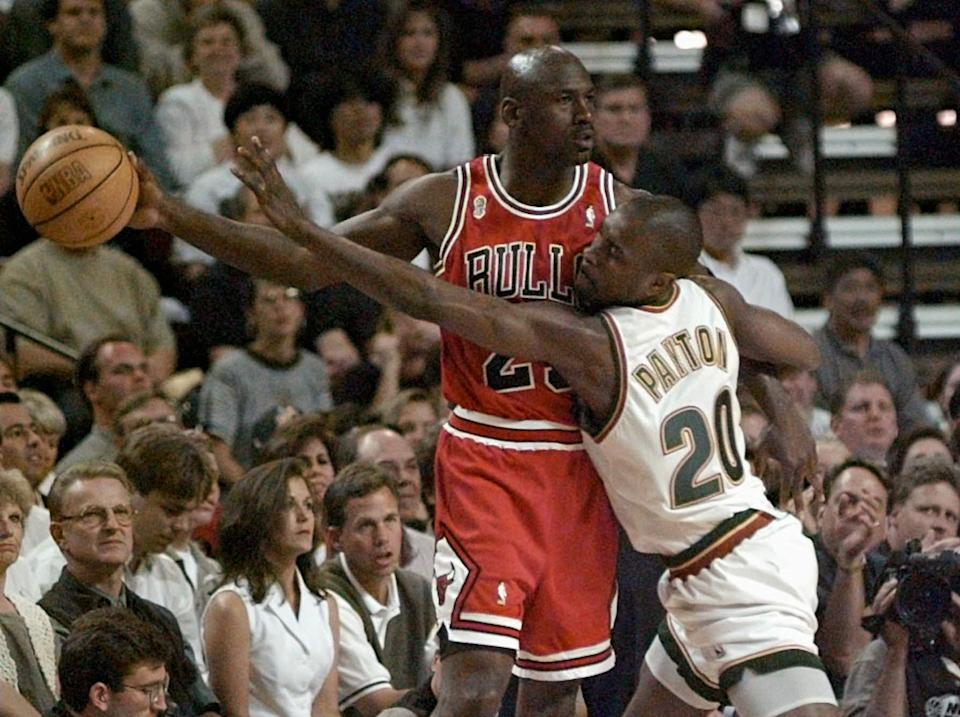Chicago Bulls guard Michael Jordan holds the ball away from  the Seattle SuperSonics' Gary Payton (20) during the first quarter of Game 4 in the NBA Finals Wednesday, June 12, 1996, in Seattle.  (AP Photo/Elaine Thompson)