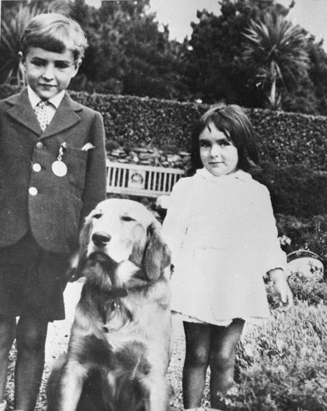 <p>Elizabeth was born in Hampstead Garden, a suburb of London, England. Here, a five-year-old Elizabeth and her brother, Howard, pose with their family's golden retriever. </p>