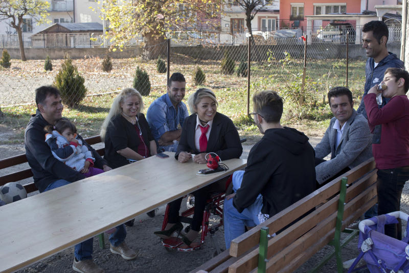 In this photo taken Tuesday, Nov. 13, 2018, Mahana Jami, 34, center, talks to friends inside a government run camp for refugees and migrants in Bosilegrad, some 250 kilometers southeast of Belgrade, Serbia. As a little girl in a wheelchair in Iran, Jami used to watch other children play on a slide and wondered why she couldn't do the same. She then made a promise to herself to always dream big and never let her disability stand in the way. (AP Photo/Marko Drobnjakovic)