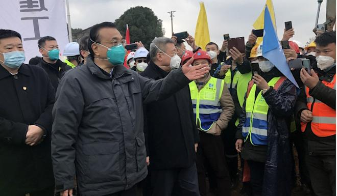 Premier Li Keqiang visits workers at the construction site of a new hospital in Wuhan in January. Photo: EPA-EFE