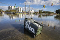 A trash container floats at the intersection of Fishburne St. and Hagood Ave. as a king tide rolls into historic Charleston, S.C. Sunday, Nov. 15, 2020. Charleston has remained relatively unscathed this hurricane season. That means more time to mull a $1.75 billion proposal by the Army Corps of Engineers that features a sea wall along the city's peninsula to protect it from deadly storm surge during hurricanes. (AP Photo/Mic Smith)