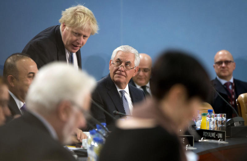 British Foreign Secretary Boris Johnson, left, prepares to take his seat next to U.S. Secretary of State Rex Tillerson as they attend a meeting of the NATO-Georgia Council at NATO headquarters in Brussels on Wednesday, Dec. 6, 2017. (AP Photo/Virginia Mayo)