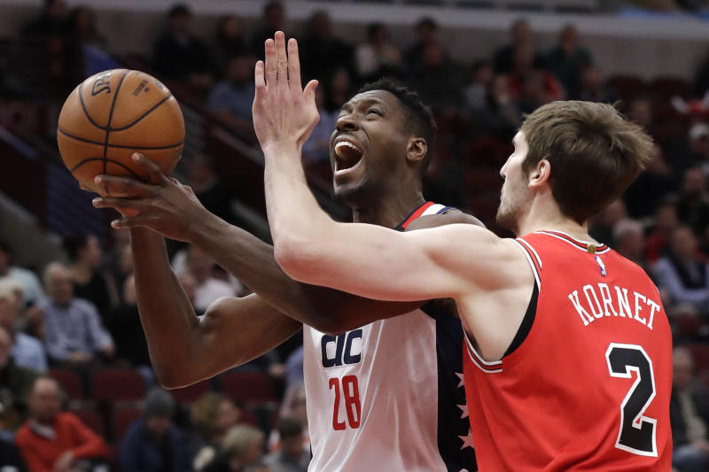 Washington Wizards center Ian Mahinmi, left, drives to the basket as Chicago Bulls forward Luke Kornet defends during the first half of an NBA basketball game in Chicago, Wednesday, Jan. 15, 2020. (AP Photo/Nam Y. Huh)