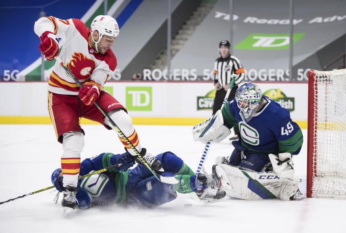 Calgary Flames' Milan Lucic (17) falls over Vancouver Canucks' Jalen Chatfield, bottom left, as he takes a shot on goalie Braden Holtby (49) during the third period of an NHL hockey game, Sunday, May 16, 2021, in Vancouver, British Columbia. (Darryl Dyck/The Canadian Press via AP)