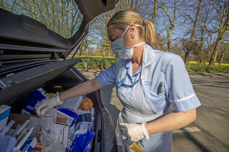 An NHS nurse collects more dressings from her car as she does a home visit in Sefton Park, Liverpool after Prime Minister Boris Johnson has put the UK in lockdown to help curb the spread of the coronavirus. PA Photo. Picture date: Thursday March 26, 2020. The UK's coronavirus death toll reached 463 on Wednesday. See PA story HEALTH Coronavirus. Photo credit should read: Peter Byrne/PA Wire