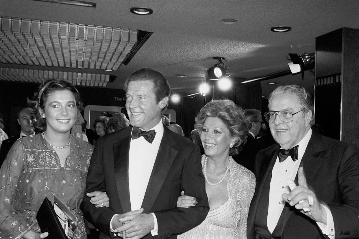 ROGER MOORE WITH HIS WIFE LUISA AND FILM PRODUCE ALBERT 'CUBBY' BROCCOLI ARRIVE AT THE ROYAL GALA CHARITY PREMIERE OF FOR YOUR EYES ONLY.   (Photo by PA Images via Getty Images)