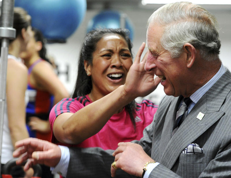 Britain's Prince Charles has sweat wiped from his face after receiving a hug from one of the members of the New Zealand women's sevens rugby team at the AUT Millennium, New Zealand's national training center for high performance sports, in Auckland, New Zealand, Monday, Nov. 12, 2012. (AP Photo/SNPA, Ross Setford)