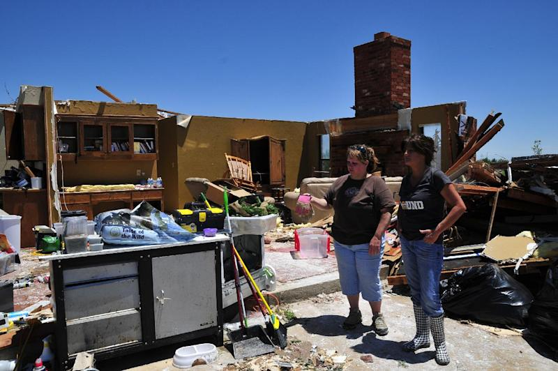 Tammy Wade, left, and her sister in-law Dana Givens look over what is left of Tammy's home that was destroyed by the tornado, Saturday June 1, 2013 in El Reno Okla. (AP Photo/Nick Oxford)